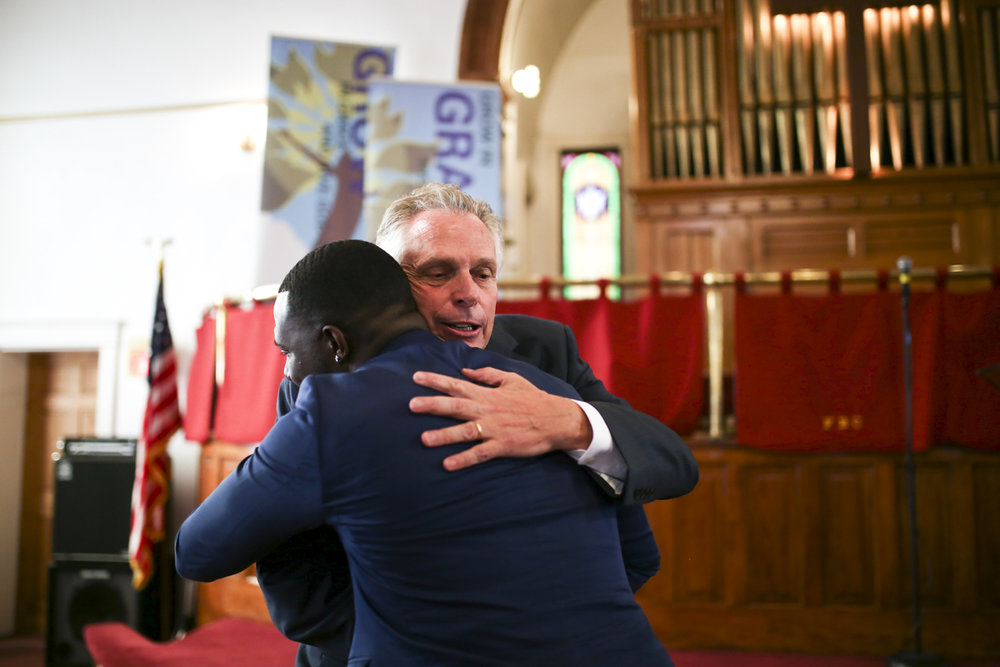Virginia Gov. Terry McAullife hugs Charlottesville Vice Mayor Wes Bellamy after addressing members of First Baptist Church in Charlottesville, Va., on Sunday, August 13, 2017. [Scott P. Yates for The Wall Street Journal]
