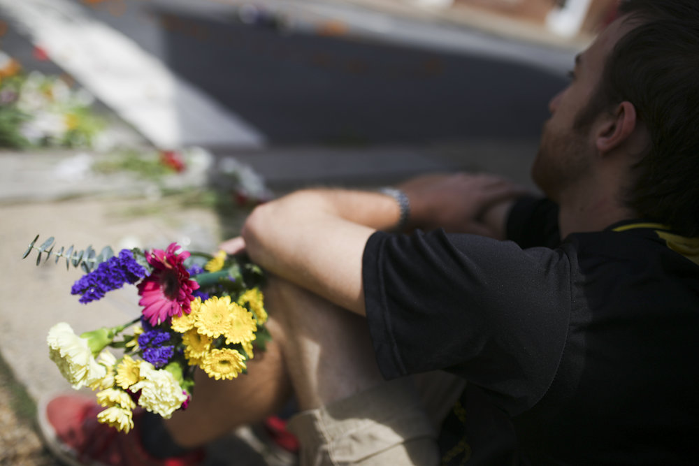 A man named Ben, who did not want to publish his last name, holds flowers as he mourns on Sunday, August 13, 2017, at the street memorial for Heather Heyer, and the more than 30 other vicitims, of a white supremacist terrorist attack against counter protesters the day before. [Scott P. Yates for The Wall Street Journal]