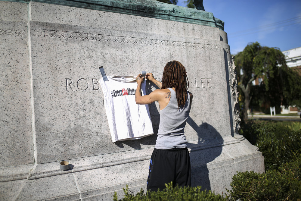 "Kayvon Powell, from Charlottesville, tapes a t-shirt that reads ""#EveryLifeMatters"" onto the base of the Robert E. Lee statue in Emancipation Park in Charlottesville, Va., on Sunday, August 13, 2017. [Scott P. Yates for The Wall Street Journal]"