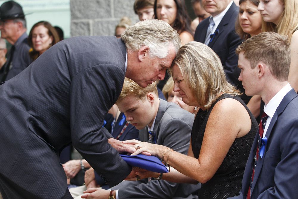 Virginia Gov. Terry McAuliffe, left, presents a flag to Virginia State Police Lt. H. Jay Cullen's widow, Karen, second from right, as she is joined by her two sons, Max, 14, left, and Ryan, 17, right, during a memorial service for the officer at Southside Church of the Nazarene in Chesterfield on Saturday, August 19, 2017. Lt. Cullen died in a helicopter crash while providing security and intelligence during the violent and deadly protests in Charlottesville, Va., on August 12. [Scott P. Yates/progress-index.com]