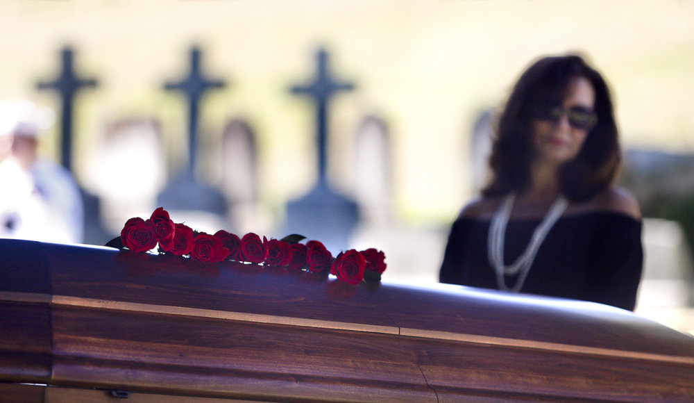 "Elena Thompson, from Fairfax, Va., pays her respects at the casket of her uncle-in-law, William Manley Thompson, who was killed in 1941 at Pearl Harbor while serving on the USS Oklahoma and whose remains were originally classified as ""Unidentifiable,"" during a full military funeral at a family plot in Blandford Cemetery in Petersburg, Va., on Friday, Sept. 8, 2017. [Scott P. Yates/progress-index.com]"
