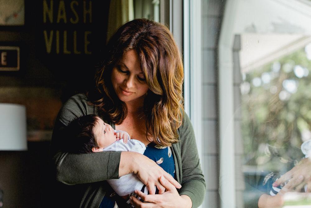 Mother holding newborn in window light. In home newborn photographer Columbus OH