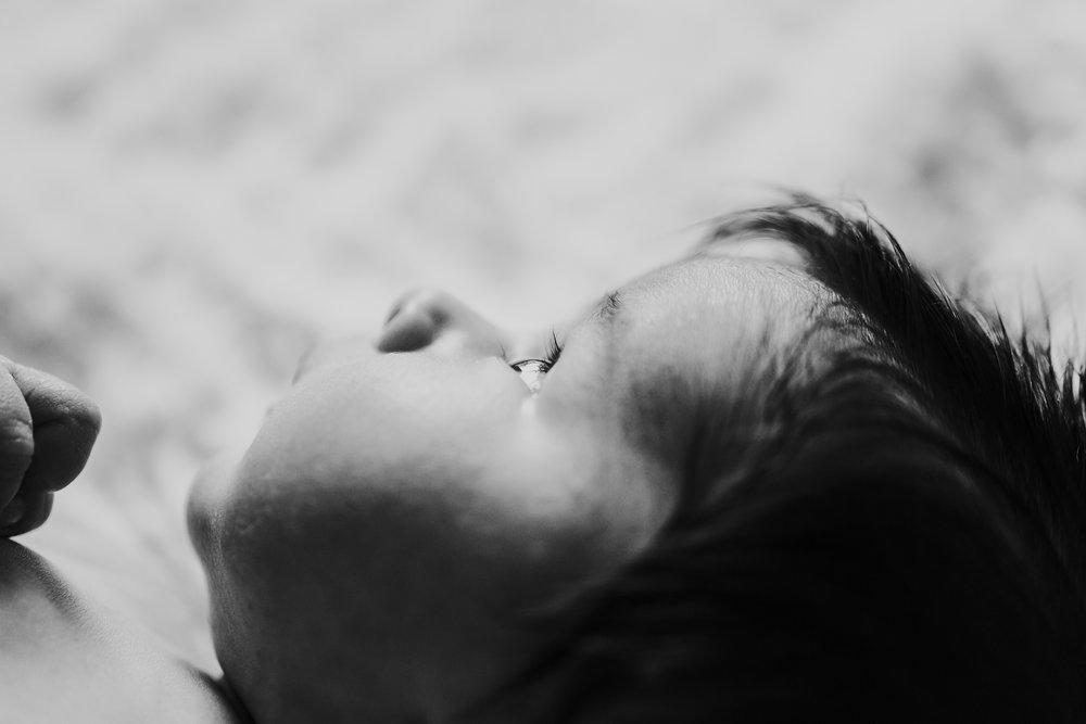 Black and white profile of newborn face. In home newborn session