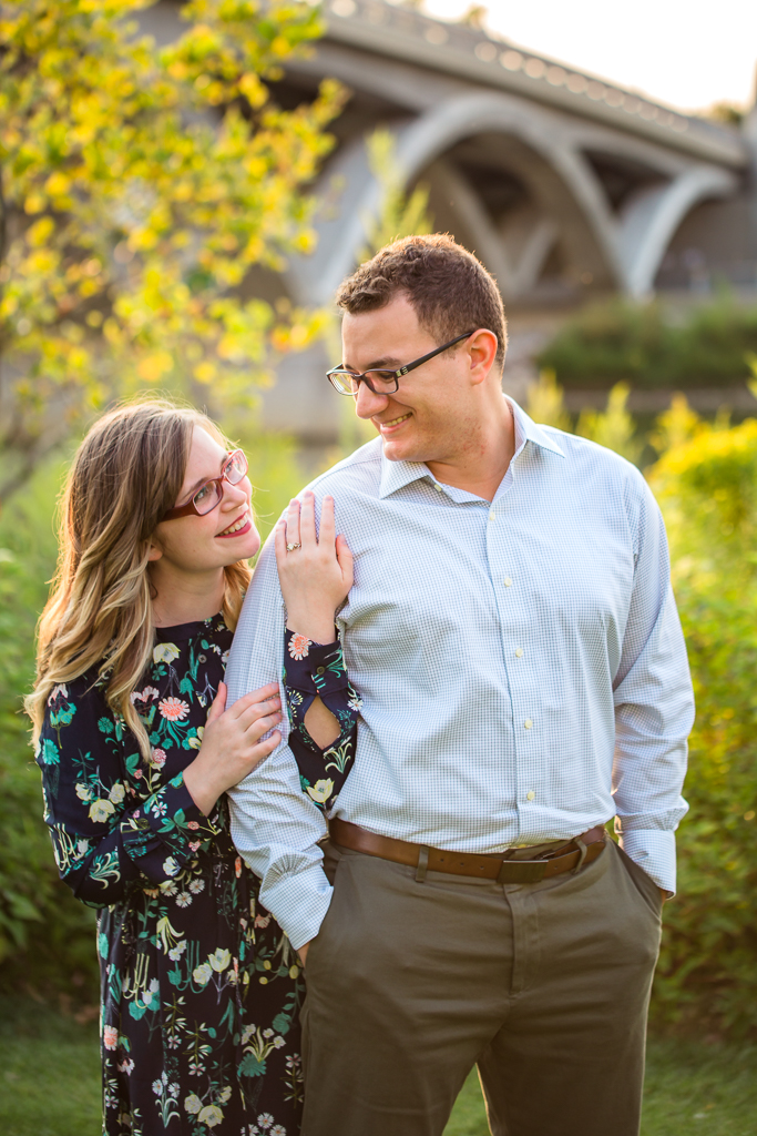 Woman poses standing behind man and snuggling his arm while featuring her engagement ring. Couple smiles at each other in front of bridge and sunset at the Scioto Mile Riverfront in Columbus OH during their engagement session.