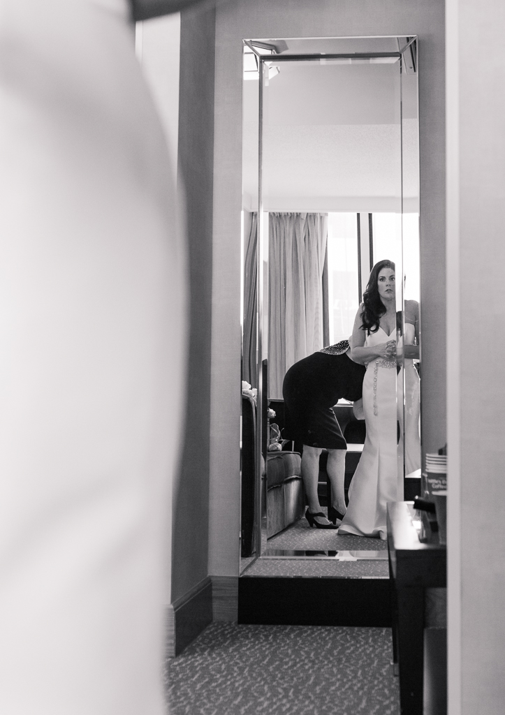 A nervous bride looks at her reflection in a mirror after she first puts on her wedding dress while getting ready for her wedding at the Radisson hotel in Downtown Columbus OH