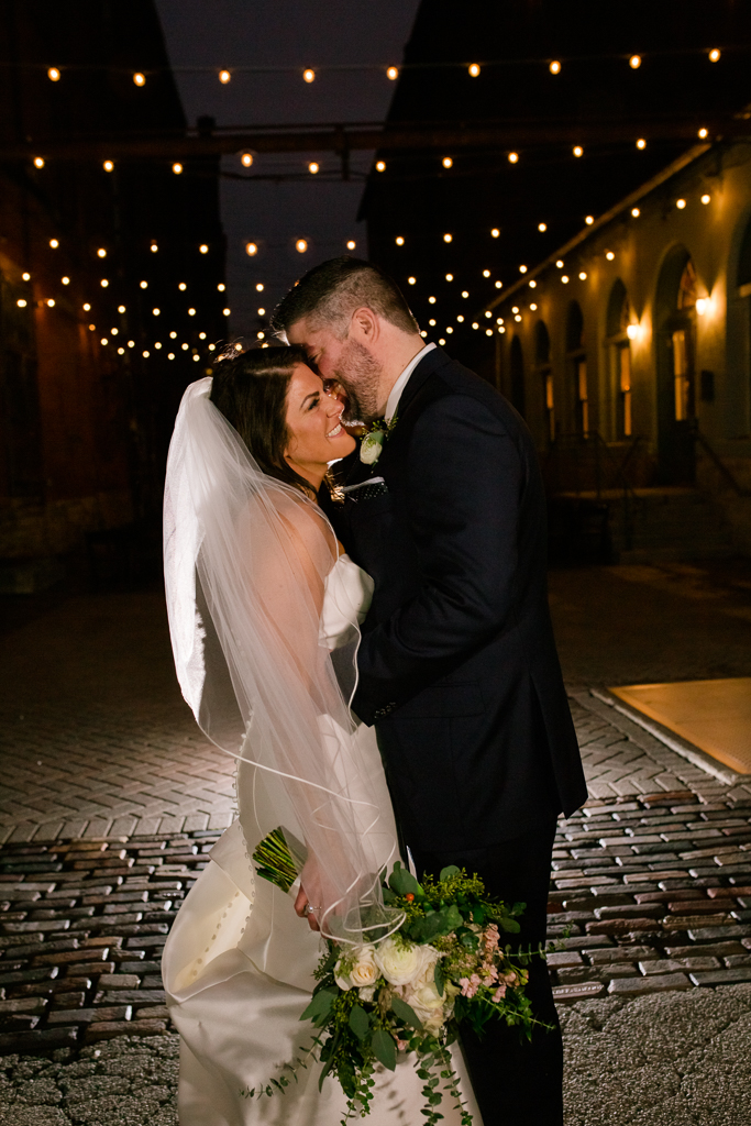 Groom kisses brides neck under string lights in alley after their wedding at Via Vecchia in Columbus OH.