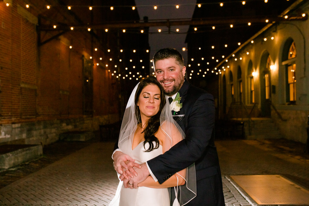Bride closes her eyes and leans on her new groom under the string lights after their Via Vecchia wedding.