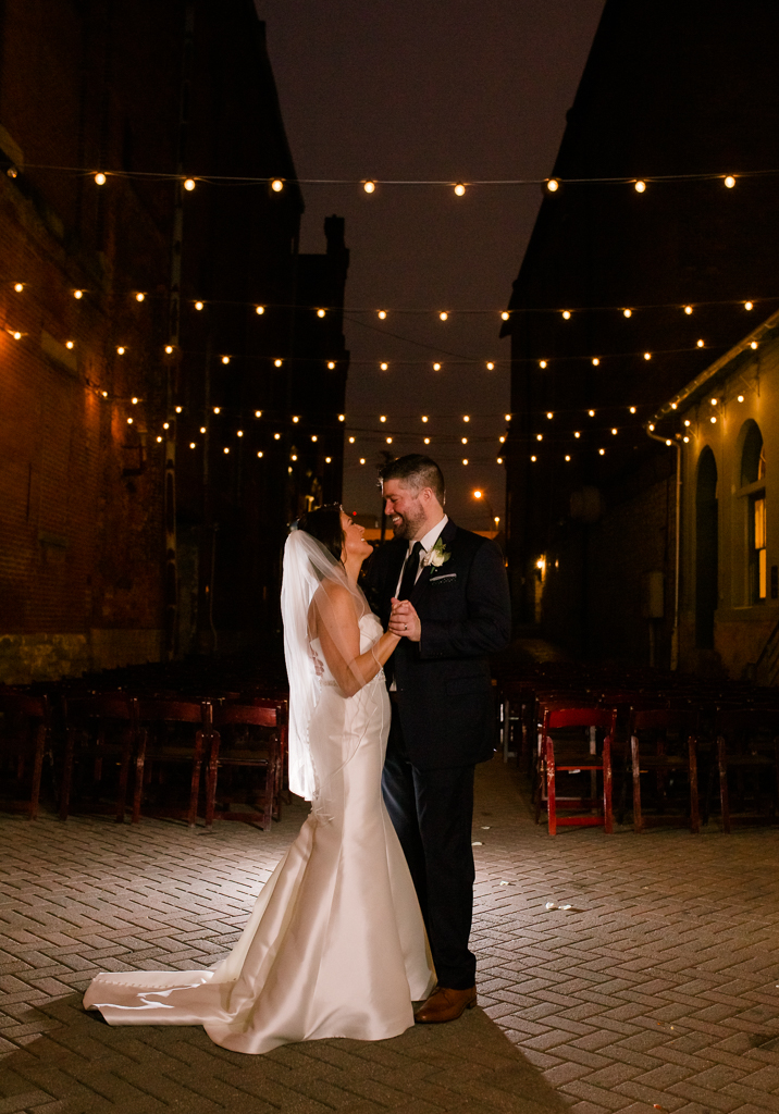 Night portrait of Bride and groom dancing under twinkling string lights in brick alleyway after their wedding at Via Vecchia.