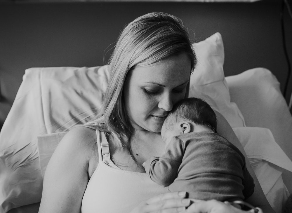 Mother snuggles her infant son during Fresh 48 session in the hospital in Columbus OH