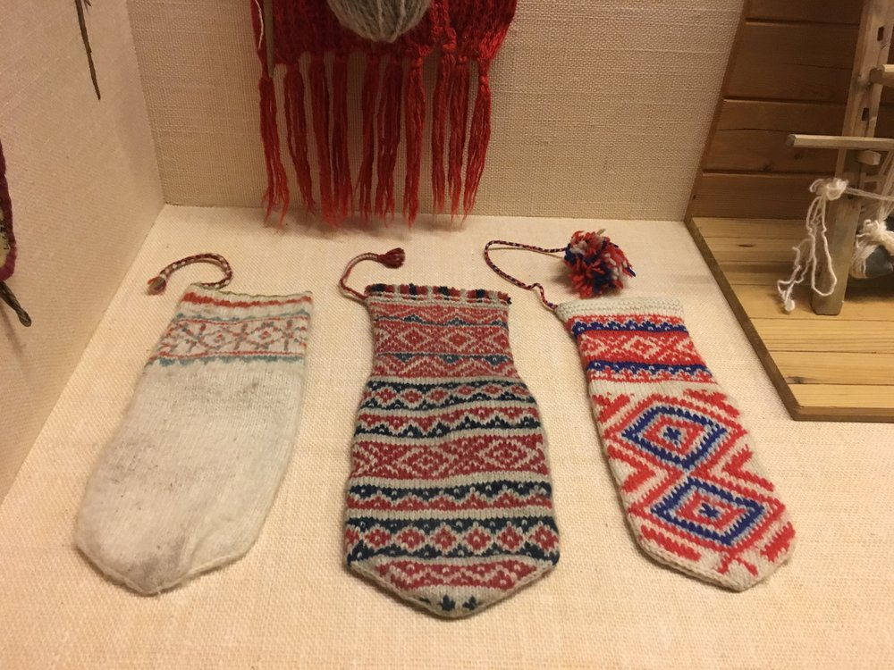 Intricate colorwork, hand knit mittens on display.