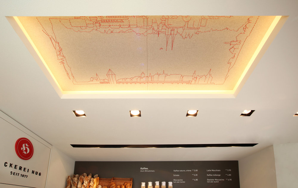 Besticktes Deckensegel in der Hug-Filile in Luzern/  Embroidered ceiling banner at the Hug branch Lucerne