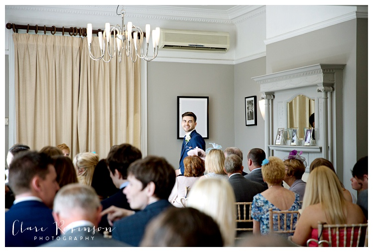 Groom looking back at guests at the front of the ceremony room in anticipation of the brides arrival - Woodlands Hotel Leeds