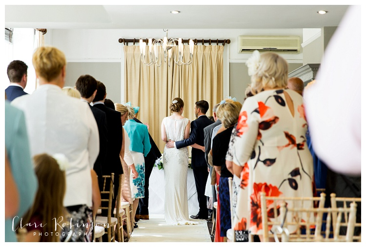 Bride and groom embrace as they stand at the end of the aisle at woodlands hotel leeds