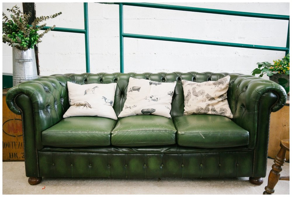 A dark green chesterfield sofa in the bar area of the wellbeing farm barn