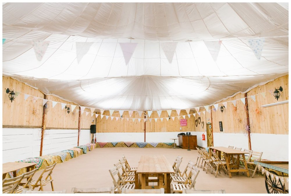 the wedding barn at the wellbeing farm, with pastel bunting, hay bales, rustic wooden chairs and tables, and a draped fabric ceiling with over 4000 fairy lights