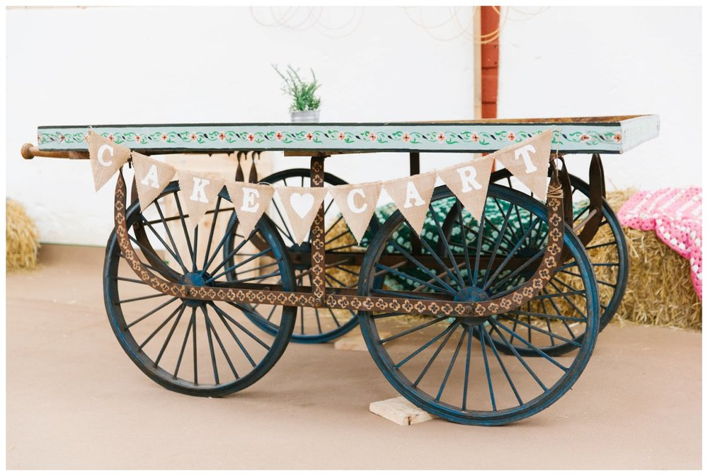 an old gypsy style flat top cart with 4 large iron wheels and hessian bunting reading 'cake cart'