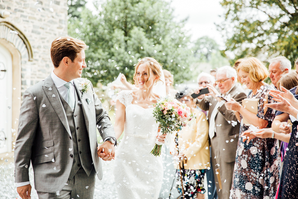 Newly married couple being showered in confetti whilst walking and looking at each other, in the grounds of a church in the lake district