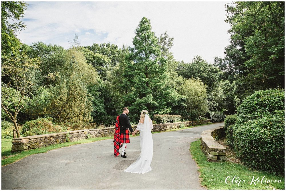 Bride and groom walking away from Rivington Hall on a path, the brides veil is flowing behind her - Lancashire wedding photographer