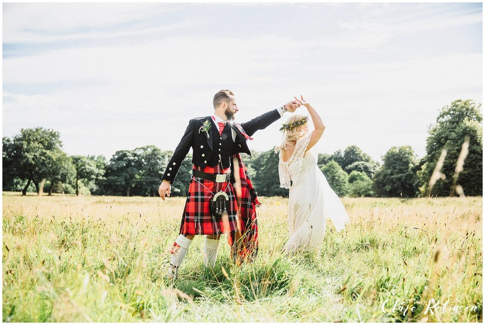 Bride and groom share a dance as the groom spins the bride in a field of long grass at Rivington Hall Barn - Natural wedding photographer lancashire