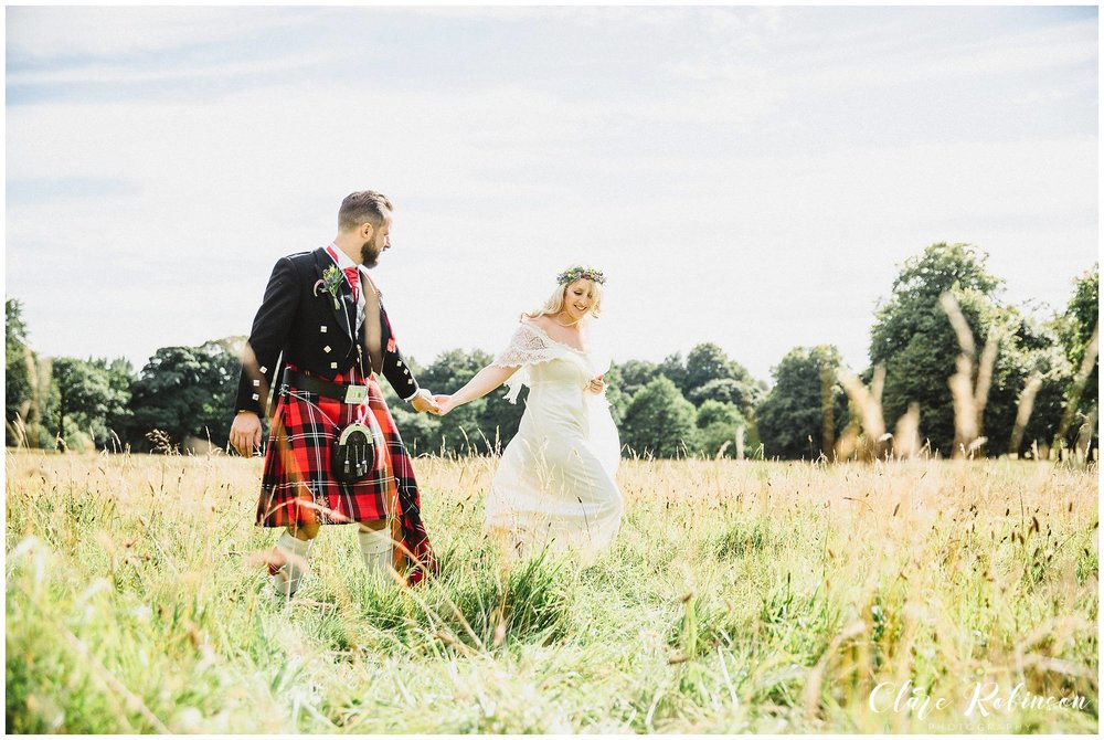 Bride and groom walking in a field of long grass at Rivington Hall Barn - Natural wedding photographer lancashire