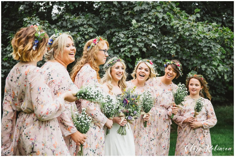 The brides and bridesmaid stand for a photograph but have a giggle at one of the bridesmaids jokes - Natural wedding photographer Lancashire
