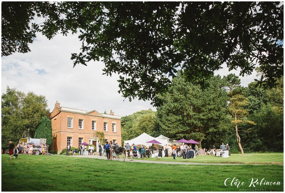 Wide shot of Rivington Hall with guests sat on deck chair enjoying the live music - Rivington Barn Wedding Photographer
