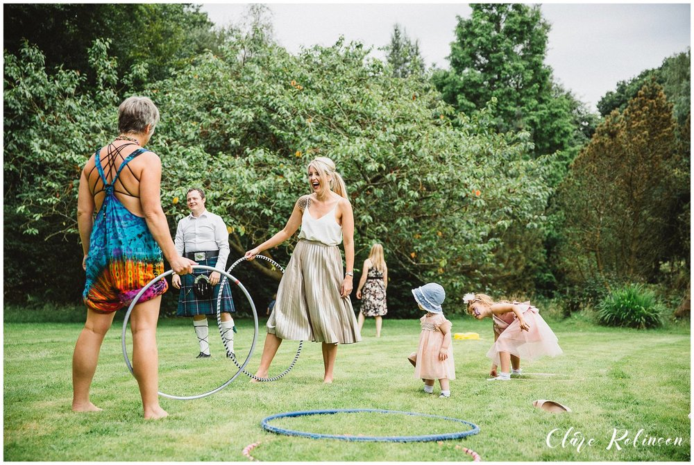 Guests playing lawn games and hula hooping on the lawn outside of Rivington Hall - Lancashire wedding photographer