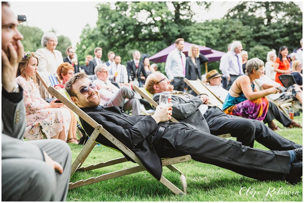 Guests relaxing in deck chairs while watching live music - Lancashire wedding photography