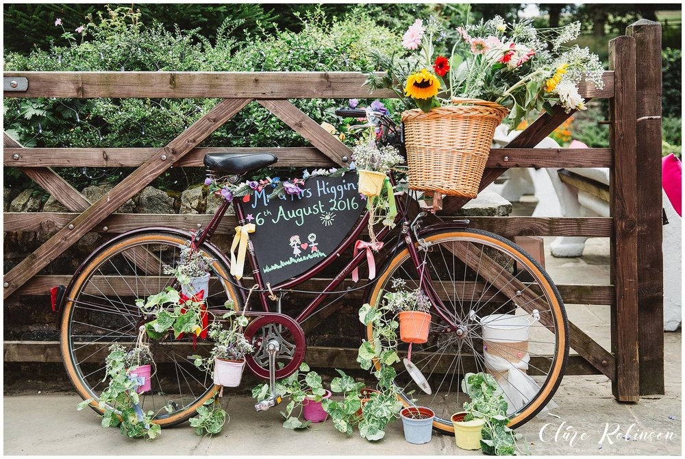 Vintage bike dressed with a basket and flowers outside Rivington Barn Wedding - Natural lancashire wedding photographer.