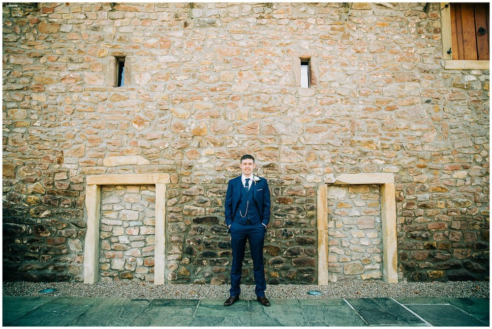 groom stood again stone wall of browsholme tithe barn