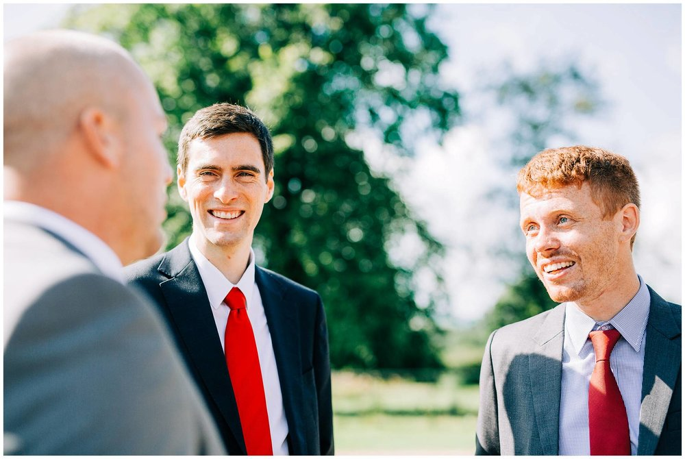 two men both wearing red ties are talking and smiling to another guest