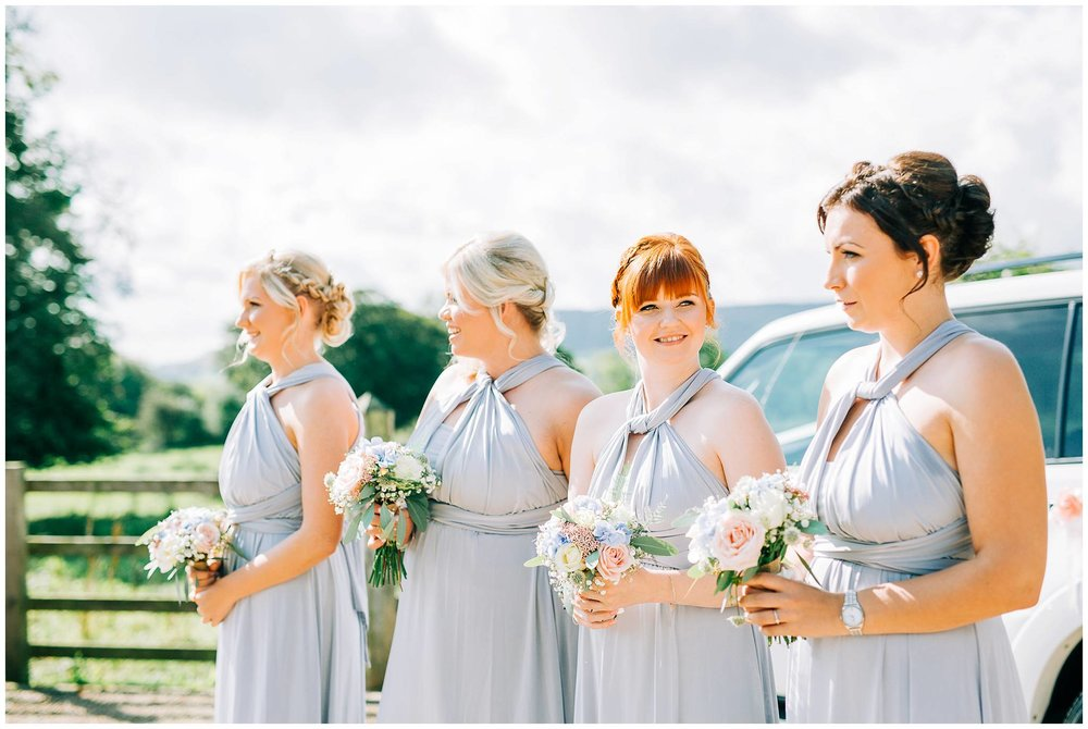 the 4 bridesmaids are stood by a car holding their bouquets and are waiting for the brides arrival