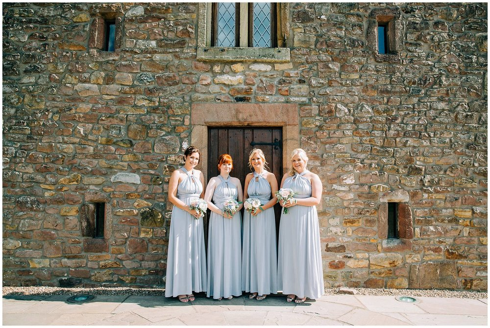 4 bridesmaids are posed in a line against browsholme tithe barn for