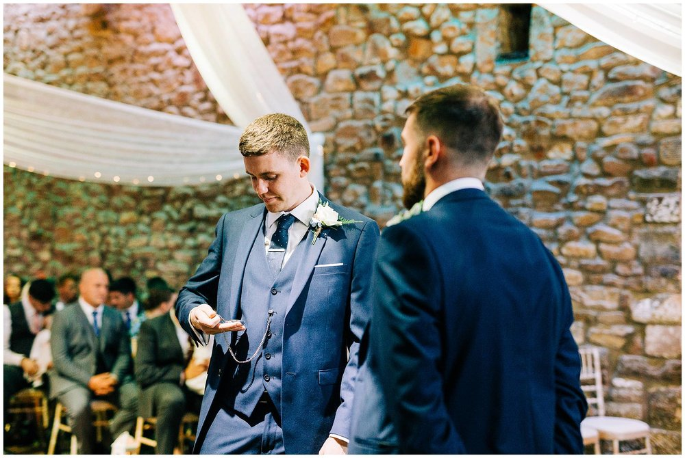 groom looks nervous as he looks down at his pocket watch in his hand