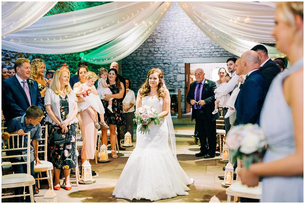 bride walks down the aisle on her own full of smiles at browsholme hall tithe barn