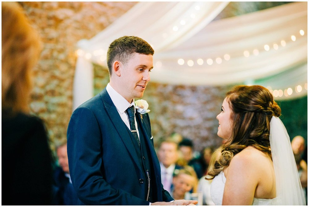 groom saying his wedding vows and looking at the bride during ceremony at browsholme hall tithe barn