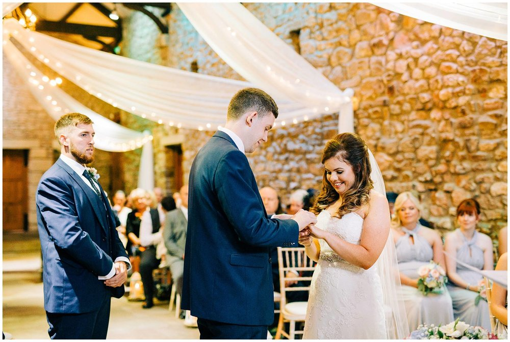 bride happily smiling at the groom placing her wedding band on her finger at browsholme hall tithe barn