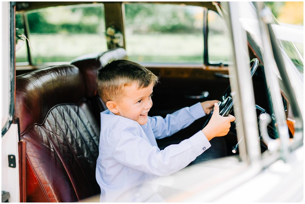 young boy sat smiling mischievously in the front seat of a vintage bentley car