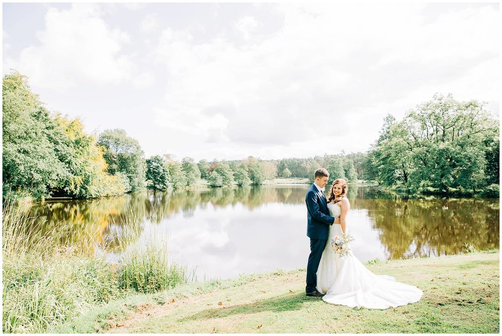 bride and groom stood at side of vast lake at browsholme hall tithe barn