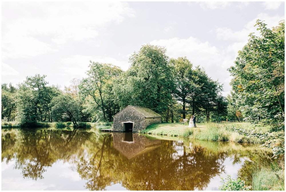 bride and groom featuring wuite small in a landscape image of the large lake at browsholme hall tithe barn