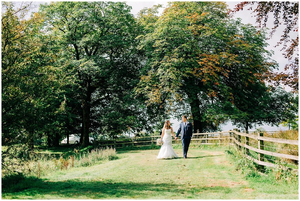 newlyweds walk hand in hand on a grass path surrounded by trees whilst looking ay each other