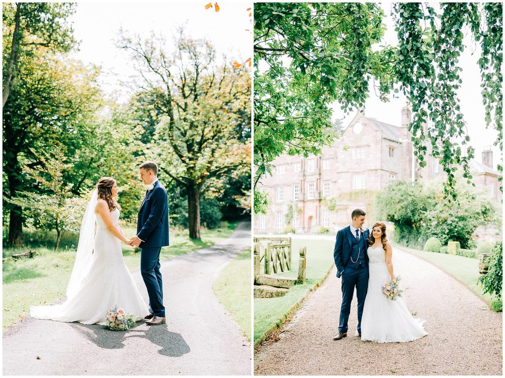 bride and groom stood in the middle of rural road facing each other and cuddling under a leafy canopy with browsholme hall in the background