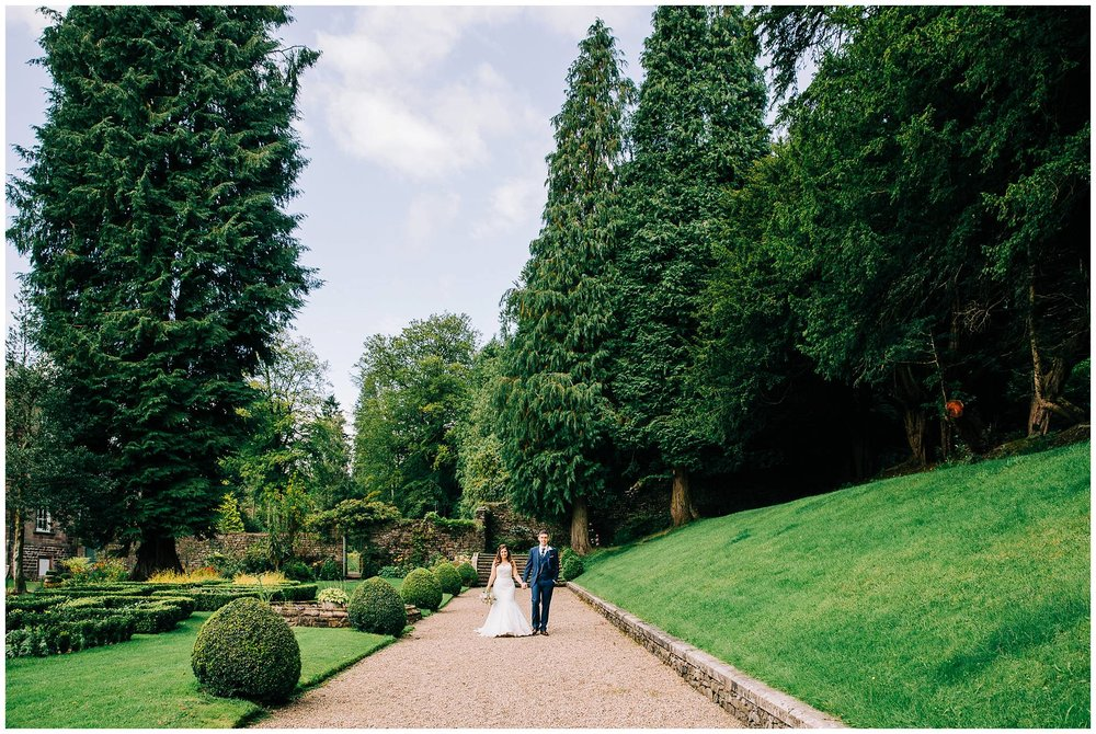 bride and groom walking along pebbled path next to browsholme hall manicured gardens