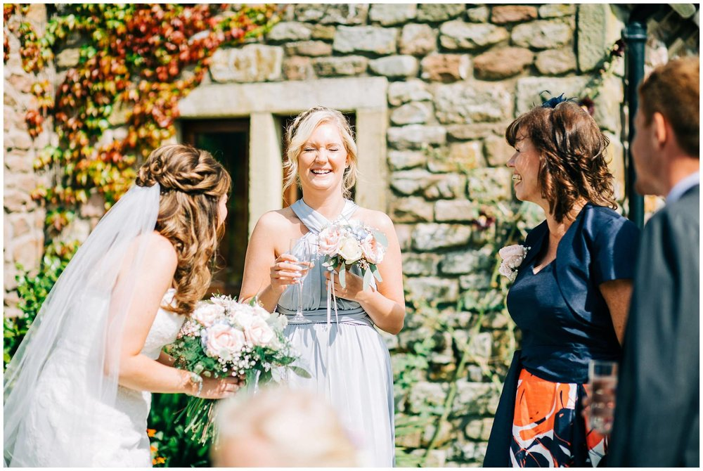 bridesmaid laughing with eyes closed holding glass of chapagne and flowers outside browsholme hall and tithe barn