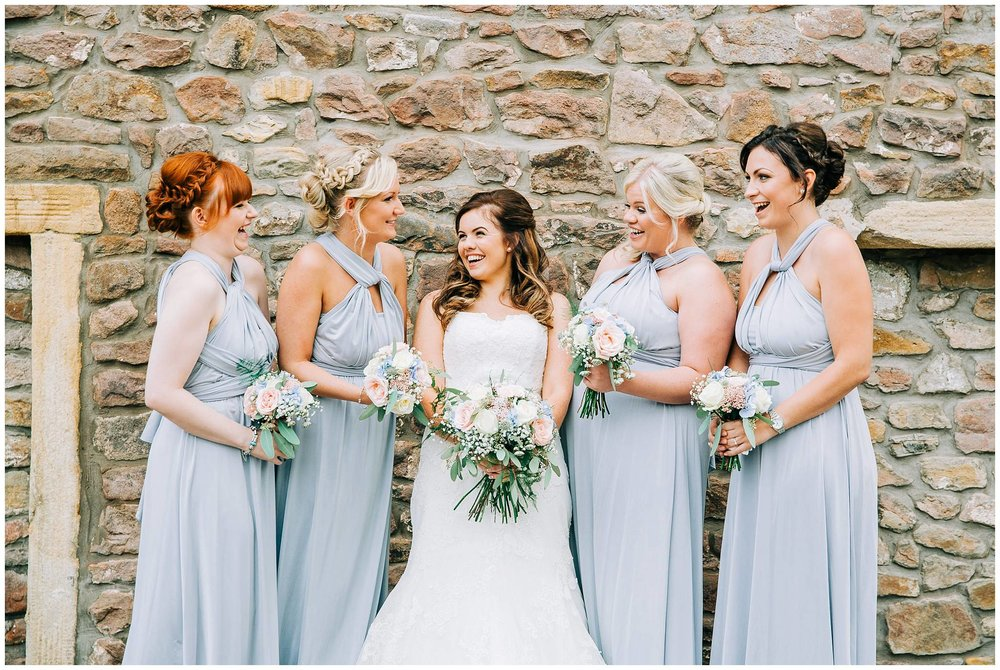 bridesmaids posed smiling at each other against browsholme hall tithe barn stone wall