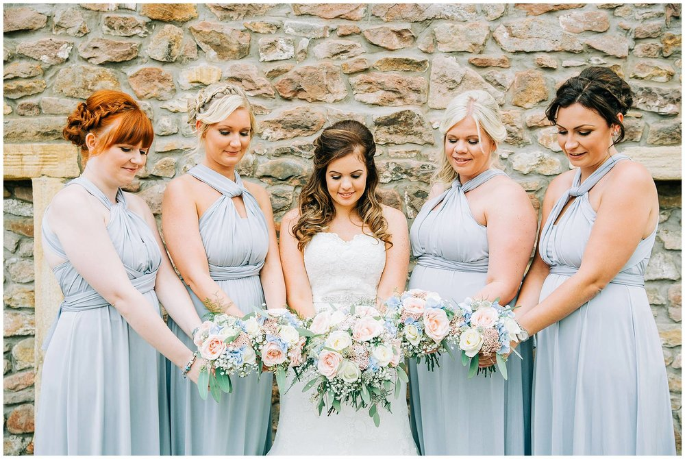 browsholme hall tithe barn stone walls acting as backdrop for groups of bridesmaids and bride looking at their bouquets.