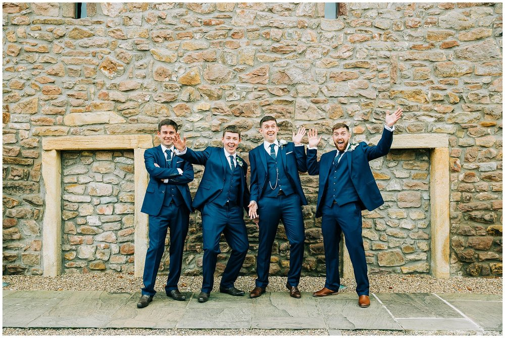 groom and groomsmen being silly tithe barn stone wall from the browsholme hall estate