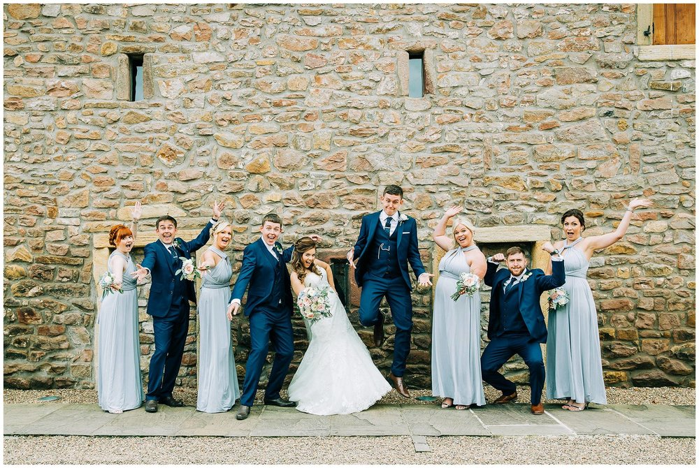 bridal party jumping and acting daft against stone wall backdrop from browsholme hall tithe barn