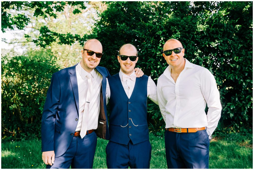 Groom stood with two groomsmen with arms round each other