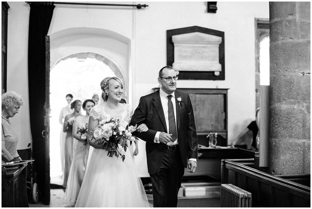 bride beginning her entrance into the church looking extremely excited